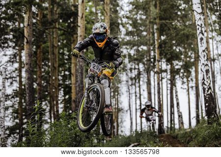 Miass Russia - May 29 2016: jump and fly racer on bike in woods during Cup
