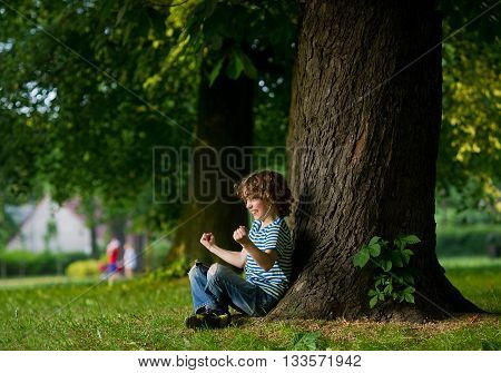The boy with earphones in ears sits under a big tree. Something has excited him. The boy has clenched fists. On a face indignation.