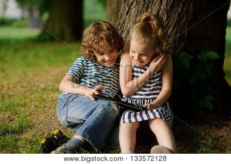 The boy with the girl of 7-8 years sit under an old tree and excitedly look at the laptop screen. Children like game. They laugh.