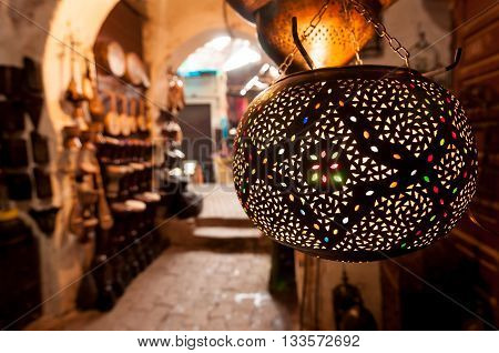 A metalwork lantern on display outside a shop in a Marrakesh souk.