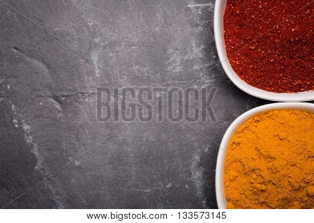 Tanduri masala and kurkuma in white bowl on slate background view from above as image background with copy-space.