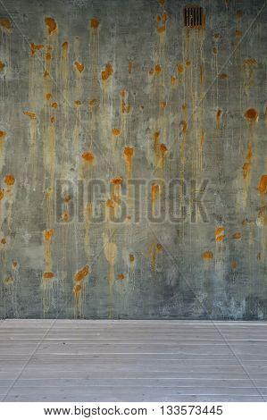 old green brown surface and concrete wall with rusted spots on white wooden floor.