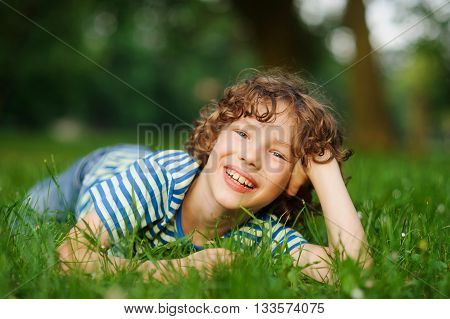 The boy lies on a green lawn in park having propped up the head a hand. He looks in a camera and smiles. The boy has curly hair and a nice face.