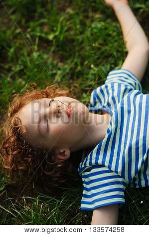 The boy lies on the earth having stretched hands in the parties. Eyes are closed from pleasure. Blond curly hair. On cheeks a flush. In a mouth floret. The child has a rest.