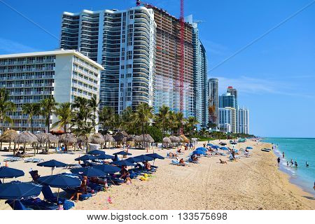 May 21, 2016 in Miami, FL:  Large highrise buildings and tourists relaxing on lounge chairs under umbrellas and people swimming in the warm waters of the Atlantic Ocean where tourists and locals spend leisure time taken from the sandy beach at Sunny Isles