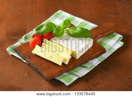 sliced soft cheese with white rind on wooden cutting board