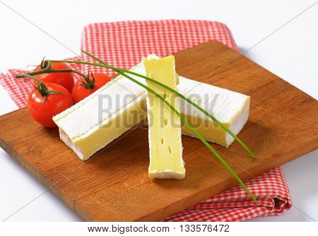 sliced soft cheese with white rind on wooden cutting board - close up