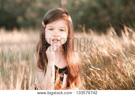 Smiling baby girl 4-5 year old posing in meadow. Looking at camera. Childhood.