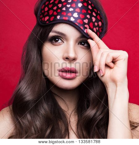 Funny young woman in sleeping mask and pajamas on a red background. The beauty of the face. Photos shot in studio