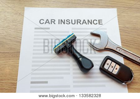 Top view of car insurance with car remote key wrench and rubber stamp.