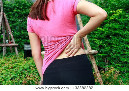 Female athlete lower back painful injury. Sporty woman backache and injury concept