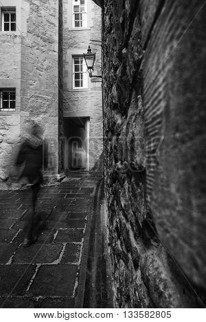 Motion blur as a man walks through one of the many narrow closes (lane) off the Royal Mile in Edinburgh Scotland