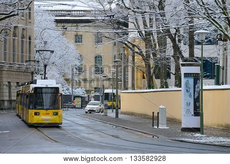 BERLIN - DECEMBER 26: Yellow tram in city street on December 26, 2014 in Berlin, Germany. The tram in Berlin is one of the oldest tram systems in the world.