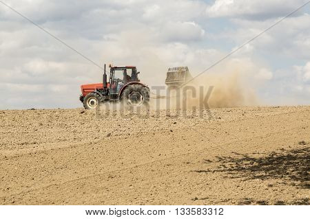 Tractor ploughing a field with a trail of dust behind it. Blue sky above.