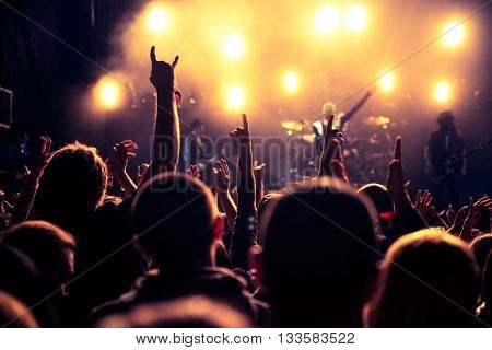 Rearview of an audience with hands raised at a music festival. High ISO