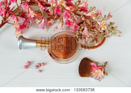 The Pink  Branche of Chestnut Tree,Bronze Powder with Mirror and Make Up Brush are on White Table,Top View
