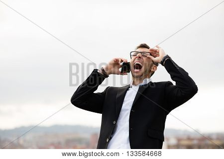 Young businessman shouting during cellphone call outside.