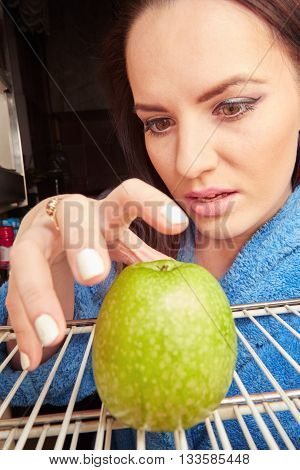 sad hungry girl taking apple from refrigerator