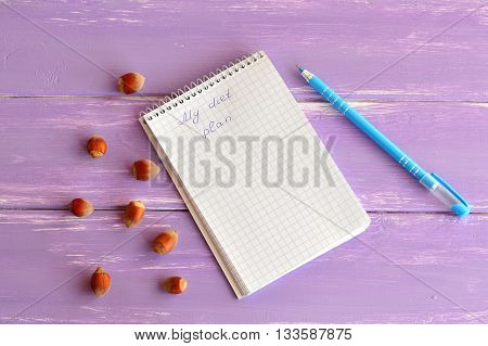 Open notebook with words My diet plan. Notepad to plan weight loss. Blue pen. A handful of hazelnuts. Diet concept. Planning concept