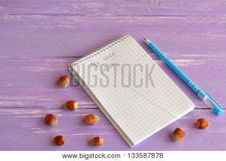Paper notebook, pen, nuts on lilac wooden background. My diet plan. Slimming concept. Lifestyle. A notepad diet menu. Notepad for diets programs