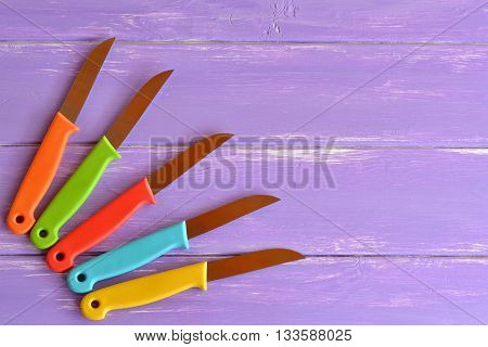 Kitchen knife set. Bright color handle. Knives with metal blade and plastic handles. Different knives for cutting. Purple wooden background with blank space for text. Top view