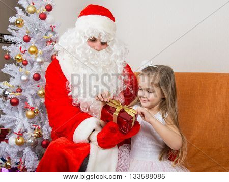 Girl Unleashes A Red Ribbon Gift That Keeps Santa Claus In The Hands Of