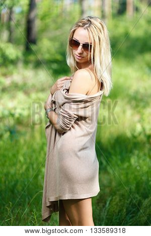 Blond girl at forest. Green grass on a background.