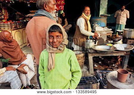 VARANASI, INDIA - JAN 5, 2016: Unidentified boy with smiley face standing at outdoor cafe with tea-masala vendor on poor street on January 5, 2016. Varanasi urban agglomeration had popul. of 1435113