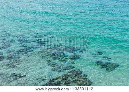 Landscape of beautiful turquoise clean water visible through submerged rock.