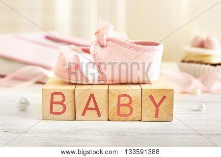 Baby booties on wooden bricks, closeup