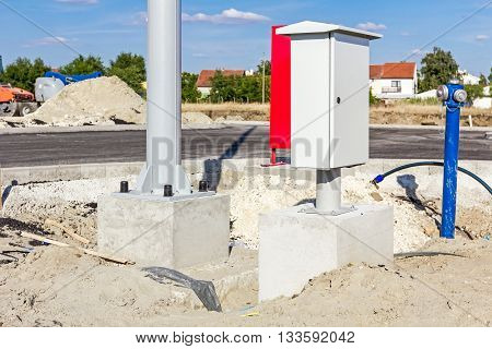New small distribution fuse box on construction site next to the pole base and hydrant.