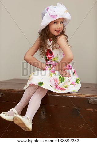 Adorable little girl in fine white dress with large red roses sitting on the old grandmother's trunk. Retro style