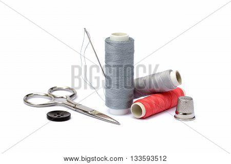 Needle, thimble, scissors, thread and knob isolated on white background