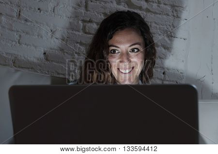 young attractive and relaxed woman at home smiling happy on sofa couch using laptop computer in dark evening light enjoying watching on line movie or addicted to internet social network