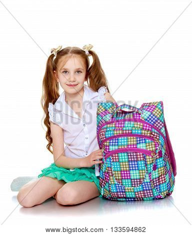 Beautiful girl schoolgirl with long pigtails on her head , sitting on the floor along with his school satchel-Isolated on white background