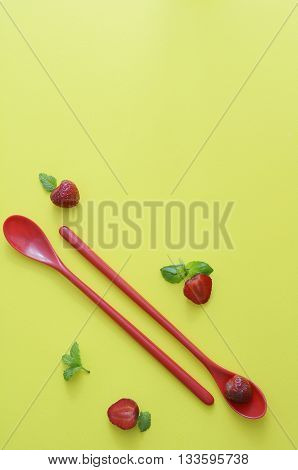 teaspoons red strawberries on a yellow background