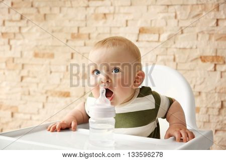 Baby drinking water in a chair on brick wall background