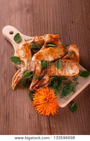 Three Marinated Chicken Wings With Oregano And Dill On Chopping Board