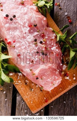 Top View On Raw Pork Meat With Pepper And Salt On Chopping Board
