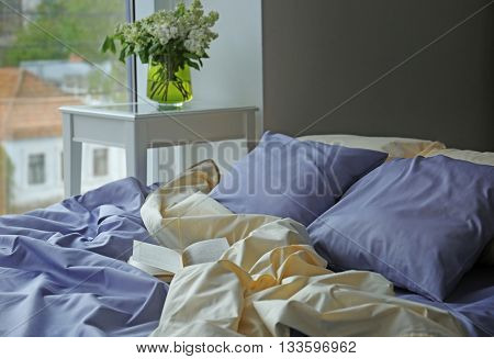 Unmade bed with crumpled blue bed linens and book