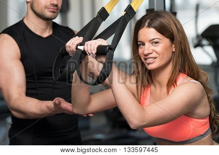Woman With Personal Trainer Train Trx Fitness Straps