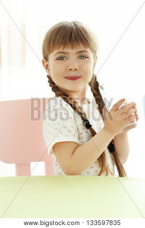 Cute little girl holding glass of water at table