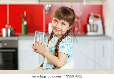 Cute little girl holding glass of water in kitchen