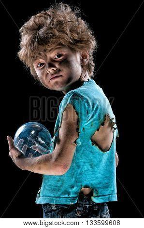 Portrait of burnt little boy with light bulb over black background