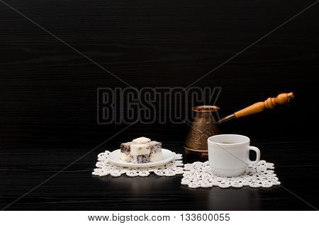 Mug of coffee Turkish delight and Cezve on a black background. Space for text