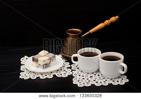 Two coffee cups Turkish Delight on white napkins and Cezve black background