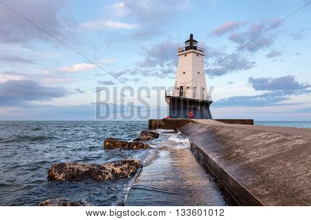 The North Breakwater Pier Lighthouse in Ludington Michigan rises above Lake Michigan with an early morning sky.