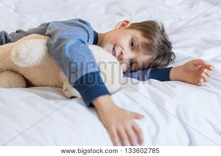 Young boy waking up in the morning with teddy bear. Happy cute little boy feeling fresh after a good sleep. Smiling child looking at camera and lying on bed in nightwear during sunny morning.