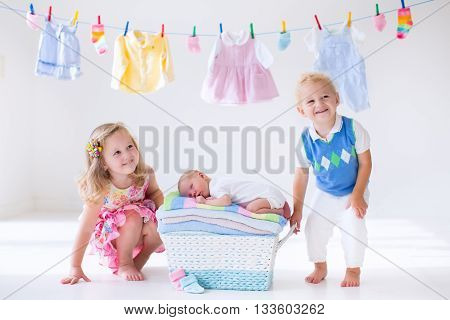 Newborn child on a pile of clean dry towels. Brother and sister kissing little sibling. Siblings bonding. Twin toddler kids kiss baby boy. New born kid after bath in a towel. Family washing clothes.