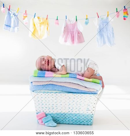 Newborn baby on a pile of clean dry towels. New born child after bath in a towel. Family washing clothes. Kids wear hanging on a line. Infant apparel textile for children. Smiling boy after shower.